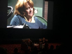 Fig. 4: Val Lehman and Jane Clifton in conversation, with Lehman's character, 'top dog' Bea Smith, on the big screen at 'On the Inside: 40 Years of Prisoner', 2019 St Kilda Film Festival, Melbourne